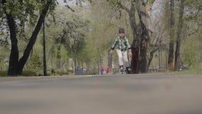Urocza ch?opiec w jaskrawym odziewa rollerblading w parku blisko rzeki Czas wolny outdoors Dzieciak ma zabaw? samotnie zbiory wideo