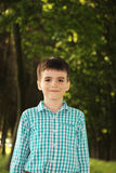 Urocza chłopiec w zielonym parku Fotografia Stock