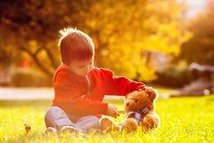 Urocza chłopiec z misiem w parku Zdjęcia Stock