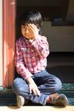 Urocza chłopiec w czerwieni sprawdzał koszulowego rozochoconego dziecko szczęśliwego dzieciaka przymknięcia jeden studenckiego ok Zdjęcie Stock