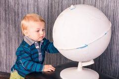 Urocza ciekawa chłopiec z kulą ziemską Zdjęcia Stock