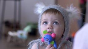 Urocza dziecka objadania zabawka w rękach na unfocused tle zdjęcie wideo