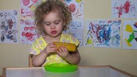 Urocza dziecko dziewczyna je gotowanego kukurydzanego cob zbiory