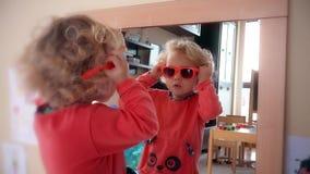 Urocza dziecko dziewczyna stawia czerwonych okulary przeciwsłonecznych na kierowniczym pobliskim lustrze zbiory