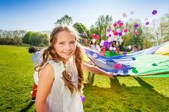 Urocza dziewczyna bawić się spadochron z jej przyjaciółmi obraz stock