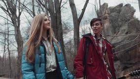 Urocza dziewczyna i przystojna młoda chłopiec w przypadkowych strojach wędruje w jesień parku, trzyma ich ręki i carelessly zbiory