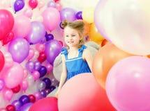 Urocza dziewczyna pozuje wśród kolorowych balonów Zdjęcie Stock