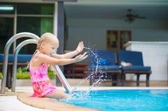 Urocza dziewczyna siedzi na basen stronie i nawadnia pluśnięcie w tropikalnym b Obraz Stock