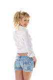 Urocza dziewczyna w cajgach zwiera i biała bluzka odizolowywająca na bielu Zdjęcia Stock