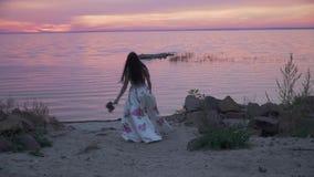 Urocza dziewczyna w długiej sukni chodzi wzdłuż banka rzeka zbiory wideo