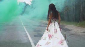 Urocza dziewczyna w długiej sukni wiruje w koloru dymu zbiory wideo