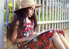Urocza dziewczyna w sukni i kapeluszowej czytelniczej książce Zdjęcia Royalty Free
