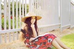 Urocza dziewczyna w sukni i kapeluszowej czytelniczej książce w parku Zdjęcie Royalty Free