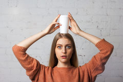 Urocza dziewczyna z szeroko otwarty oczami pozuje z filiżanki kawą Obraz Royalty Free