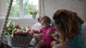 Urocza dziewczynka bawić się z tulipanowymi kwiatami zbiory