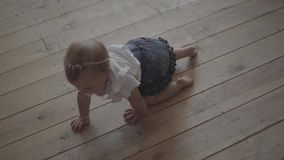 Urocza dziewczynka czołgać się na podłodze dom Dzieciak bawi? si? w domu Uroczy szczęśliwy dziecko indoors swobodny ruch zbiory wideo