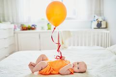 Urocza dziewczynka w pomarańczowym romper kostiumu z kolorowym balonem obrazy royalty free