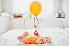 Urocza dziewczynka w pomarańczowym romper kostiumu z kolorowym balonem zdjęcie royalty free