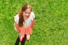 Urocza dziewczyny pozycja na zielonym lato gazonie Zdjęcia Stock