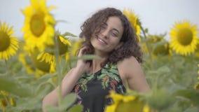 Urocza kędzierzawa kobieta zabawę na słonecznikowym polu Jaskrawy ? zdjęcie wideo