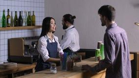 Urocza kelnerka bierze rozkaz od klienta przy kawiarnią zdjęcie wideo