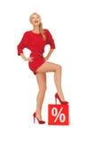 Urocza kobieta w czerwieni sukni z procentu znakiem Fotografia Stock