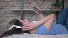 Urocza kobieta w słuchawki z telefonu komórkowego zachwyta muzyką podczas gdy odpoczywający na łóżku na wakacje w domu zdjęcie wideo