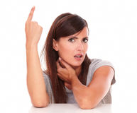 Urocza kobieta wskazuje up podczas gdy patrzejący ciebie Zdjęcia Stock