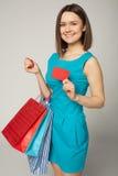 Urocza kobieta z torba na zakupy pokazuje pustą papierową kartę nad szarym tłem, Zdjęcia Royalty Free
