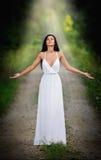 Urocza młoda dama jest ubranym elegancką długą biel suknię cieszy się promienie niebiański światło na jej twarzy w zaczarowanych  Zdjęcia Stock