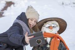 Urocza młoda dziewczyna bierze obrazki selfie z bałwanem w pięknym zima parku Zim aktywność dla dzieci fotografia stock
