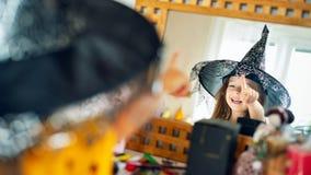 Urocza młoda dziewczyna jest ubranym czarownicy kapeluszowej patrzejący ją w lustrze, wskazujący z palcowym i roześmianym fotografia stock