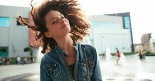 Urocza młoda dziewczyna trząść jej ciemnego kędzierzawego włosy plenerowego 4k materiał filmowy zbiory