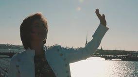 Urocza młoda dziewczyna w białej kurtce na dachu z scenicznym miasto rzeki widokiem zbiory wideo