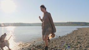 Urocza młoda kobieta bawić się biegać z jej ślicznym psem na naturze blisko jeziora zdjęcie wideo