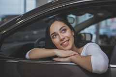 Urocza młoda kobieta kupuje nowego samochód przy przedstawicielstwem handlowym obraz stock