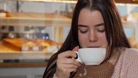 Urocza młoda kobieta ono uśmiecha się kamera, pije kawę w ranku zbiory wideo