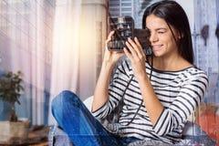 Urocza młoda kobieta trzyma natychmiastową fotografii kamerę zdjęcie stock