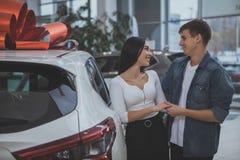 Urocza młoda para małżeńska kupuje nowego samochód wpólnie fotografia royalty free