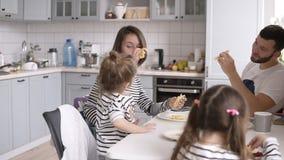 Urocza młoda rodzina z dwa dzieciakami ma śniadanie wpólnie w domu Łasowanie bliny i robić zabawa zdjęcie wideo