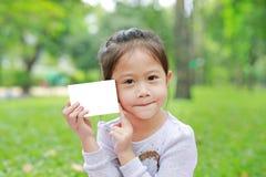 Urocza mała Azjatycka dziecko dziewczyna pokazuje w górę pustej białej księgi w zielonym ogródzie fotografia stock