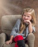 Urocza mała dziewczynka śmia się podczas gdy siedzący w krześle Zdjęcia Stock