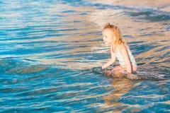 Urocza mała dziewczynka bawić się w morzu na plaży Obrazy Royalty Free