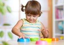 Urocza mała dziewczynka bawić się z filiżanką bawi się, ono uśmiecha się Zdjęcia Royalty Free