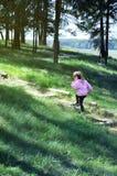 Urocza mała dziewczynka biega w górę drewnianych schodków w lasowym słonecznym dniu Zdjęcia Stock