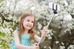 Urocza mała dziewczynka bierze fotografię ona z selfie kijem zdjęcie royalty free
