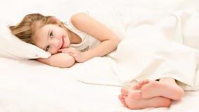 Urocza mała dziewczynka budząca się up w jej łóżku zdjęcie royalty free