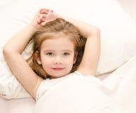 Urocza mała dziewczynka budząca up w łóżku fotografia royalty free