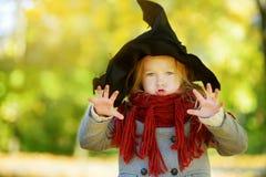 Urocza mała dziewczynka jest ubranym Halloween kostium ma zabawę na dyniowej łacie na jesień dniu Obrazy Stock