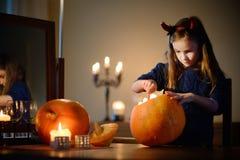 Urocza mała dziewczynka jest ubranym Halloweenowego kostium ma zabawę z rzeźbiącą banią Obrazy Royalty Free
